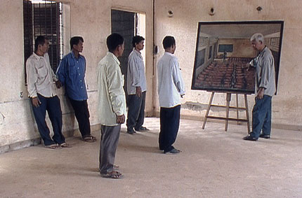 Vann Nath confronts former guards with one of his paintings of inmates bolted to the floor of their cell in S21 prison. in S21: The Khmer Rouge Killing Machine