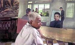 Artist Vann Nath with one of his paintings recording his history in S21 prison. in S21: The Khmer Rouge Killing Machine